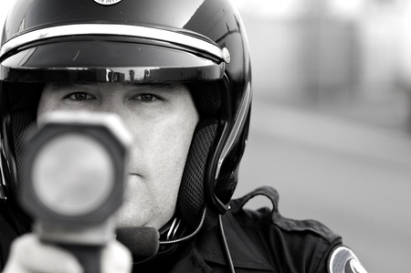 a police officer pointing his radar gun at speeding traffic. photo