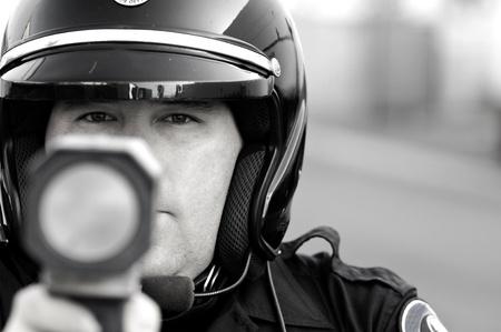 speeding: a police officer pointing his radar gun at speeding traffic. Stock Photo