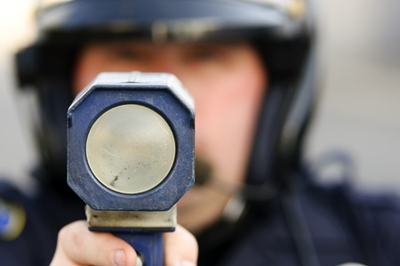 lightbar: a police officer pointing his radar gun at speeding traffic. Stock Photo