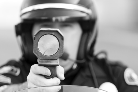 motor officer: a police officer pointing his radar gun at speeding traffic. Stock Photo