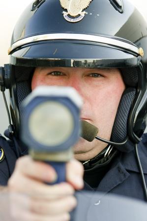 radar gun: un oficial de polic�a apuntando con su pistola de radar en el tr�fico por exceso de velocidad. Foto de archivo