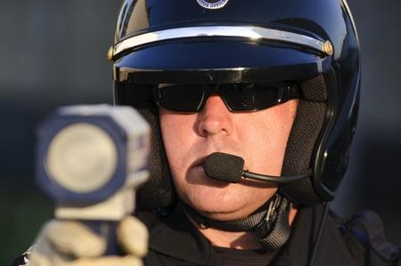polizist: ein Polizist zeigte mit dem Radar-Pistole auf die Beschleunigung Verkehr. Lizenzfreie Bilder