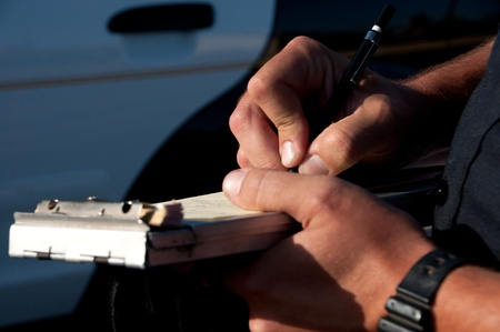 a close up of a police officer writting a traffic ticket.  photo