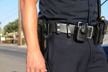 ein Polizist auf der Straße stehend auf einen Anruf. Standard-Bild
