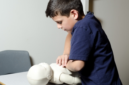 compressions: A 9 years old child practing CPR on a dummy