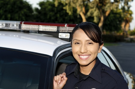 car crime: A smiling Hispanic police officer next to her patrol car.