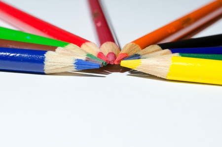 colorful pencils aranged in  a semi-circle on a white background.  A shallow depth of field was used.