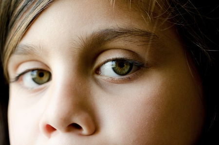 A close up of a 7 year old girl.  The focus was put on her left eye. The right eye was left slightly ourof focus on purpose.  photo