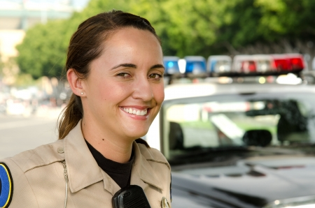 policewoman: A female police officer smiles during her shift
