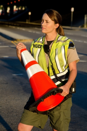 a police officer carrying a cone during a traffic control shift Stock Photo - 15401292