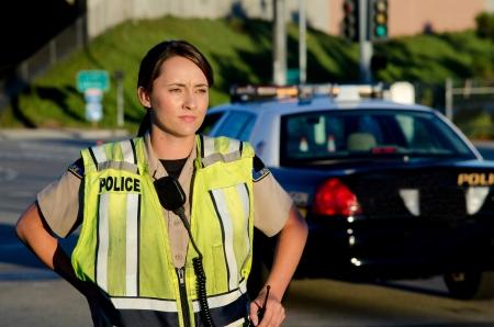 patrol cop: Un oficial de polic�a de sexo femenino mirando y mirando serio durante un turno de control de tr�fico Foto de archivo