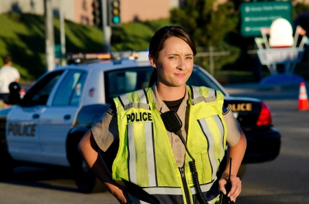 lightbar: A female police officer staring and looking serious during a traffic control shift   Stock Photo