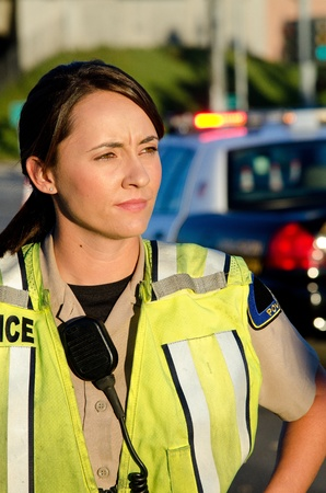 patrol officer: A female police officer staring and looking serious during a traffic control shift   Stock Photo
