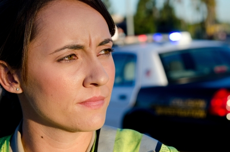 first responder: A female police officer staring and looking serious during a traffic control shift   Stock Photo