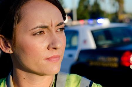 Un oficial de policía de sexo femenino mirando y mirando serio durante un turno de control de tráfico