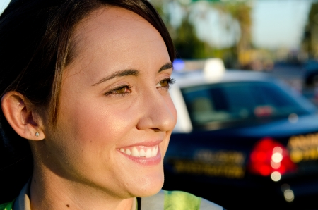 a close up of a smiling female police officer with her patrol car in the background   Stock Photo - 15401280