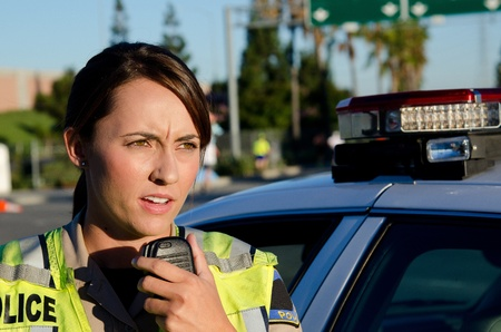 a female police officer standing next to her vehicle as she talks on the radio  photo