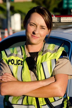 a female police officer with a frown on her face as she crosses her arms in front of her partrol car  Stock Photo - 15401319