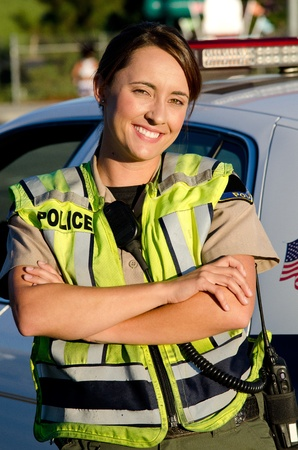 a female police officer smiling as she crosses her arms in front of her partrol car