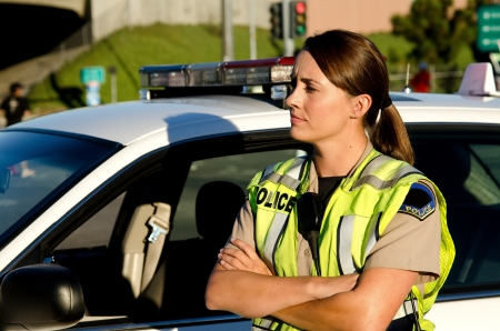 police uniform: a female police officer crosses her arms as she stands next to her patrol car