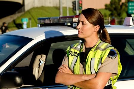 policier: une femme policier croise ses bras comme elle se tient � c�t� de sa voiture de patrouille Banque d'images