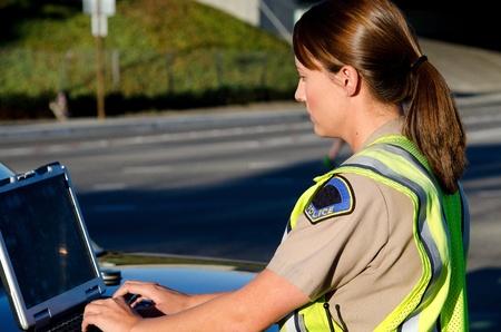 mujer policia: una hembra de tipo oficial de polic�a en su computadora port�til mientras est� en una llamada