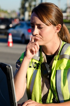female police: a female police officer types on her lap top computer while on a call.