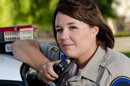 police uniform: a female police officer holds the radio as she Stock Photo