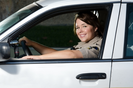 police radio: a friendly looking female police officer sits and smiles in her patrol car  Stock Photo