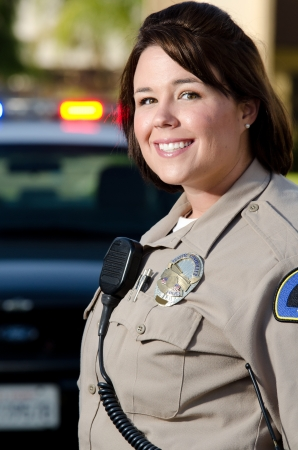 a female police officer smiles and stands in front of her patrol car