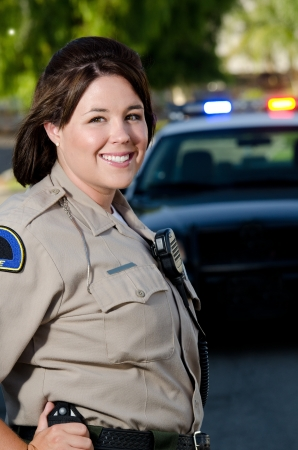 a female police officer smiles and stands in front of her patrol car  photo