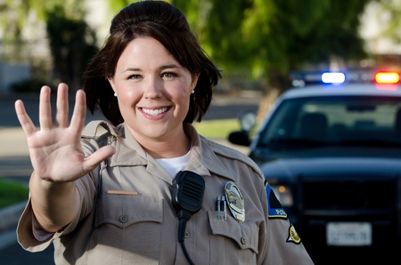 a smiling female police officer holds up her hand to get traffic to stop   photo