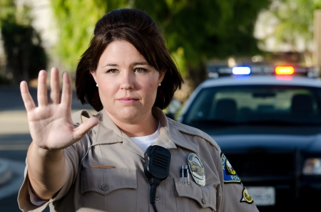 a female police officer holds up her hand to get traffic to stop