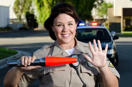 femme policier: un officier souriant tenant un geste de la main vers l'arrêt de la circulation Banque d'images
