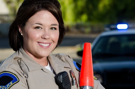 A smiling traffic office standing in front of her patrol car while holding her flashlight  photo
