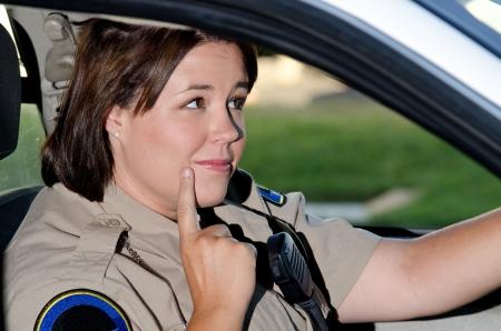 femme policier: une femme policier assis dans sa voiture de patrouille, comme elle se demande ce qu'il faut faire