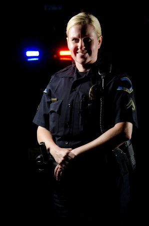 lightbar: a female police officer smiling and standing in front of her partrol car