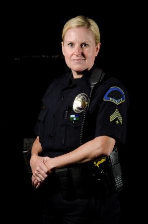 eine lächelnde Polizistin in der Nacht während ihrer Schicht