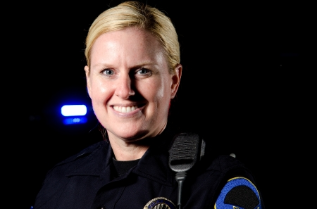 a smiling female police officer in the night during her shift   photo