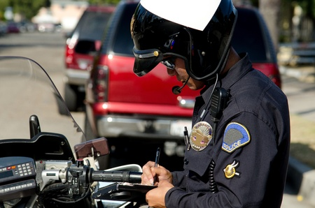 a policeman: a motorcycle police officer writing a ticket to a speeding driver.