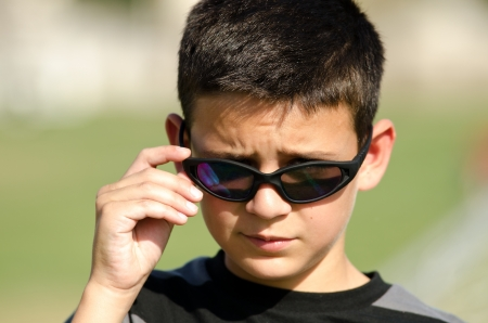 funny glasses: a portrait of a little boy showing that hes a ladies man.