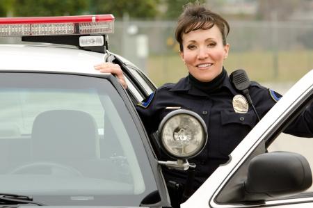 polizist: eine freundliche und l�chelnde hispanische Polizistin mit ihrem Streifenwagen.
