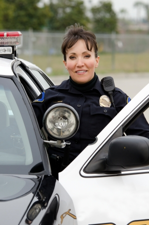 patrol officer: a friendly and smiling Hispanic female officer with her patrol car.
