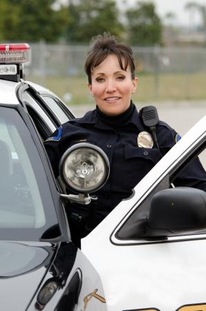 patrol cop: un amable y sonriente oficial hispano mujer con su coche patrulla.