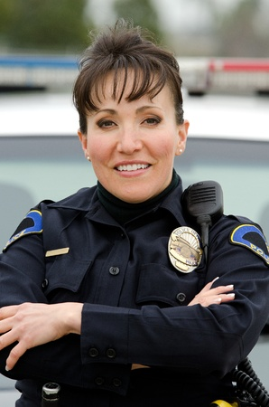 traffic police: a friendly and smiling Hispanic female officer with her patrol car.