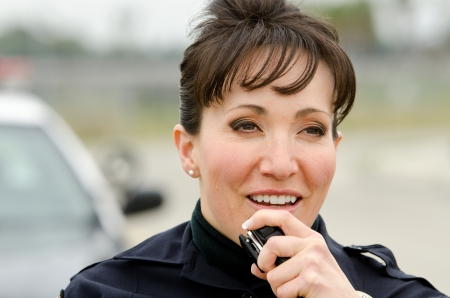 a female police officer talks on the radio with her patrol car in the background.  photo