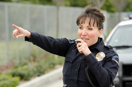 lightbar: a female police officer talks on the radio with her patrol car in the background.  Stock Photo