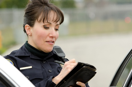 a female police officer writes a ticket while standing next to her patrol car. photo