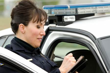 patrol officer: a female police officer writes a ticket while standing next to her patrol car.