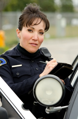 lightbar: a female police officer writes a ticket while standing next to her patrol car.